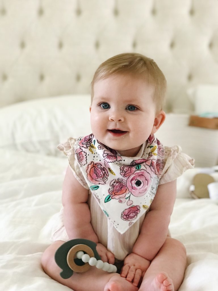 Baby in a bib with teething ring